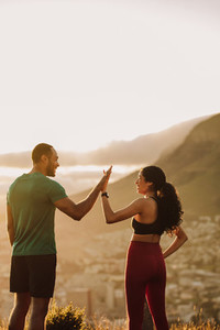 Fitness couple standing outdoors giving high five