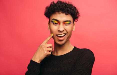Gay man with rainbow eyeshadow winking at camera
