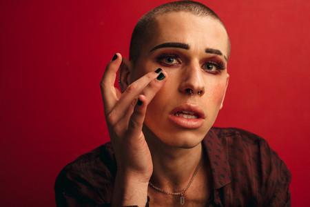 Transgender male applying make up