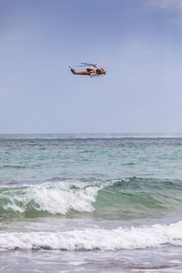 Rescue helicopter training over sunny ocean Adelaide Australia