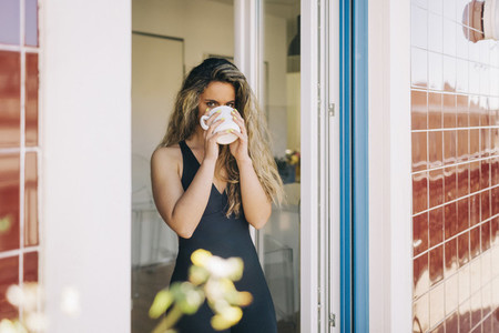 Portrait young woman drinking coffee in patio doorway