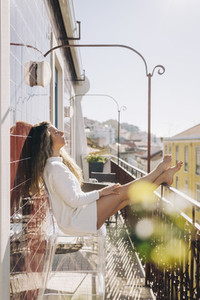 Serene young woman relaxing on sunny apartment Portugal