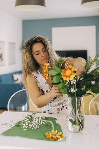 Young woman arranging flower bouquet in kitchen