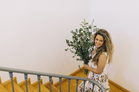 Portrait smiling woman carrying bunch of eucalyptus on staircase