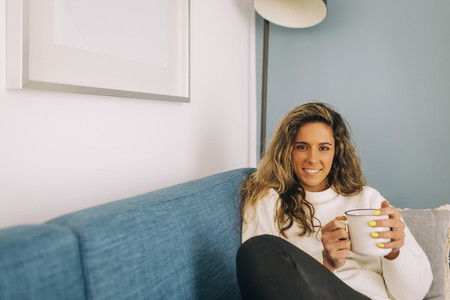 Portrait smiling young woman drinking coffee on sofa
