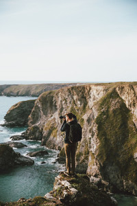 Male photographer on scenic ocean cliff Bedruthan Steps Cornwall UK