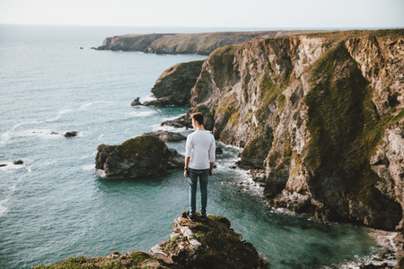 Man standing at edge of cliff over scenic ocean UK