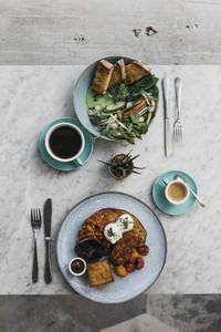 Full English breakfast and greens on toast on restaurant table