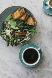 Green vegetables and toast with coffee on restaurant table
