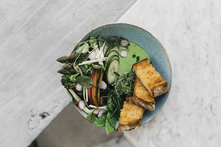 Green vegetables and toast on edge of restaurant table