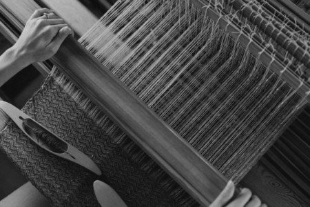 Overhead view woman working at wooden loom