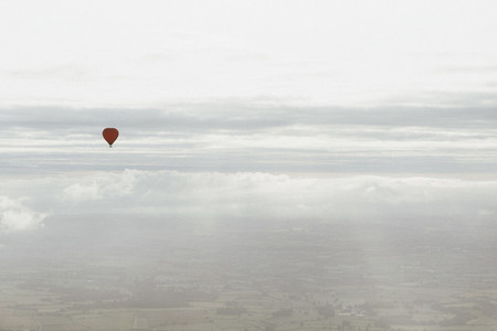 Red hot air balloon in sunny cloudy sky above Bath Somerset UK
