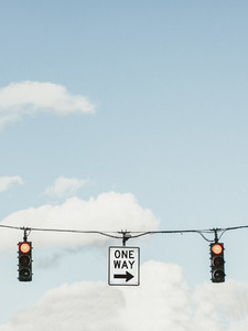 Red traffic light and one way sign below blue sky with clouds