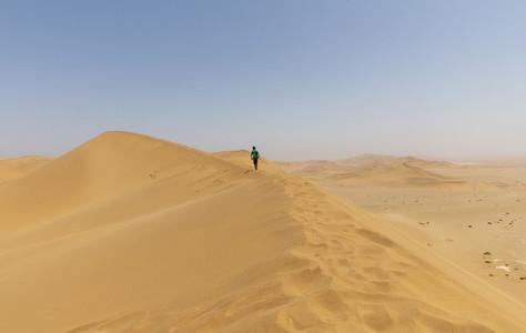 Boy walking along sunny desert sand dune ridge Namibia