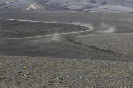 Dust cloud following car on dirt road  Iceland