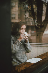Young woman drinking coffee and reading book at cafe