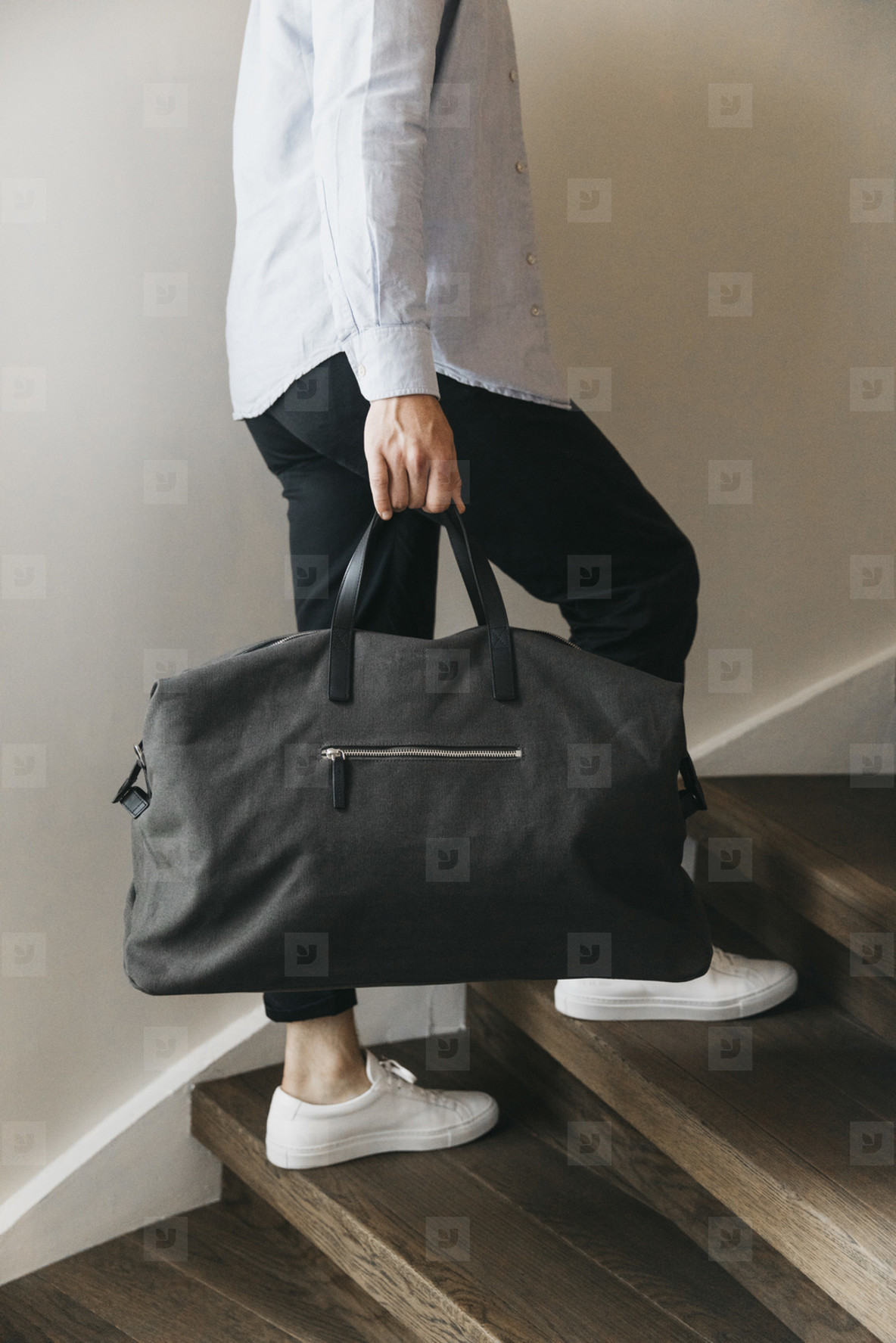 Man with duffel bag climbing wood stairs