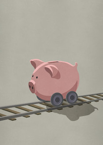 Piggy bank on wheels rolling on train tracks