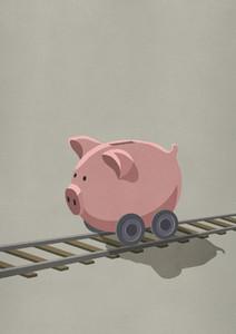 Piggy bank on wheels rolling on train tracks