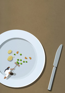 Man sweeping up vegetables scraps on large plate