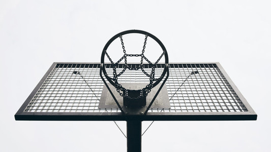 View from below metal basketball backboard and hoop