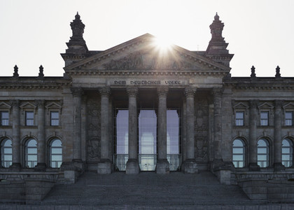 Sun shining behind Reichstag building Berlin Germany