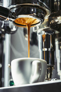 Espresso dripping from stainless steel portafilter into coffee cup