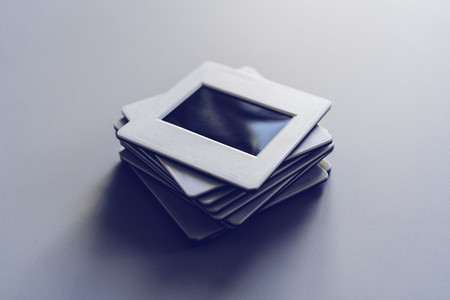 Photographic slides stacked on white background