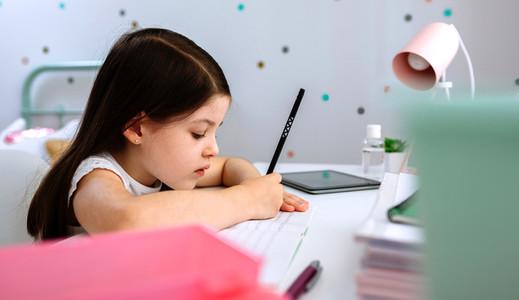 Girl doing homework sitting at a desk