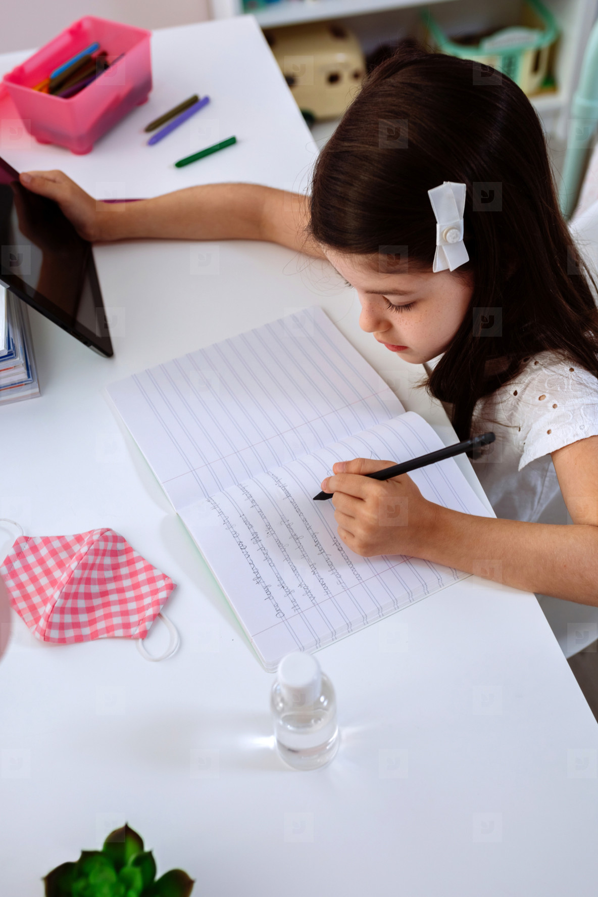 Girl studying at home with mask and sanitizer gel