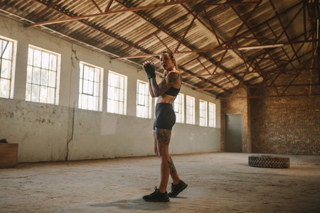 Woman shadow boxing in empty warehouse