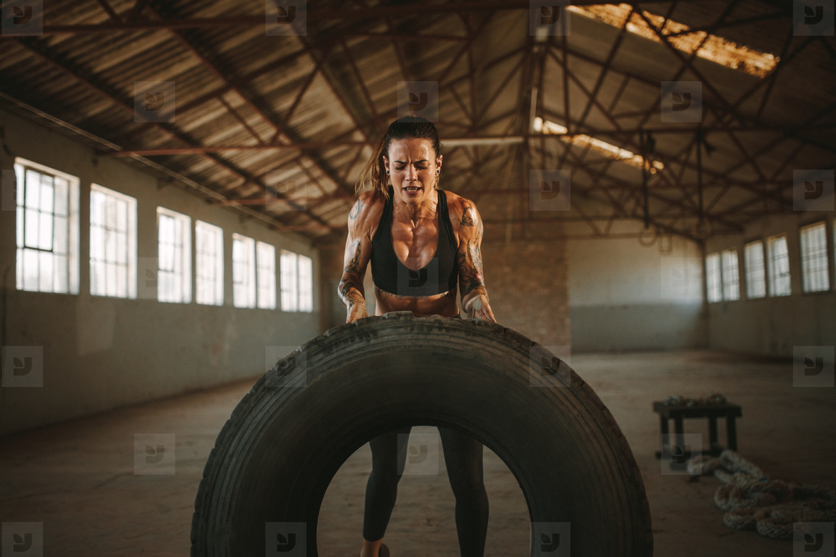 Muscular female working out with big tire