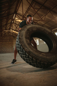 Man doing tire flipping workout at empty warehouse