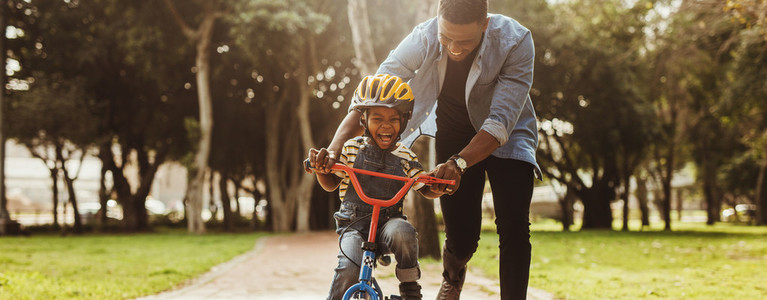 Father teaching his son cycling at park