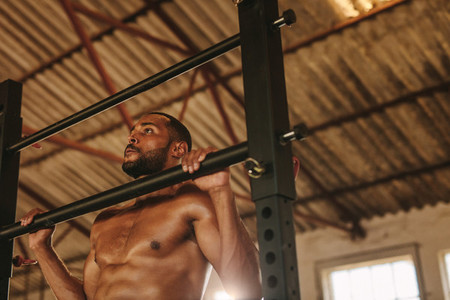 Muscular man doing pull up workout