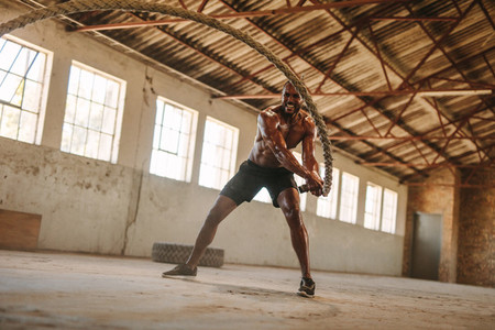 Man exercising with battle rope in abandoned warehouse