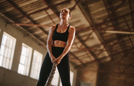 Woman exercising with battling rope at old factory shade