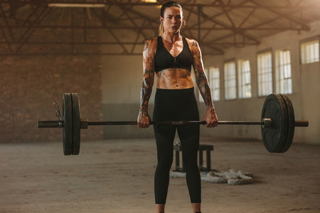 Woman doing deadlift workout with barbell