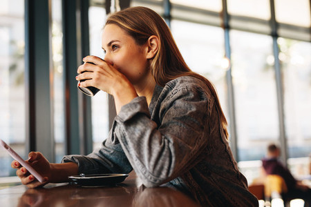 Woman having refreshing coffee at a cafe