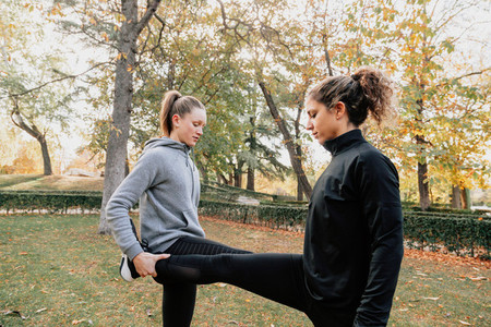 A couple of women stretching outdoors in the park