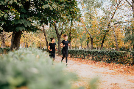 A couple of women running outside trought the park