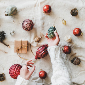 Christmas toys and womans hands with pine cone square crop