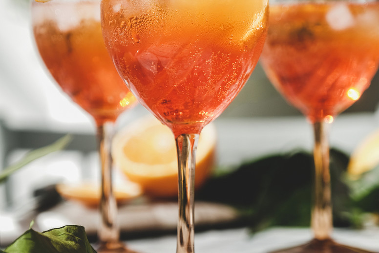 Aperol cold cocktail in glasses with fresh oranges