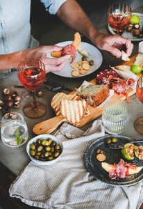 Rose wine cheese charcuterie appetizers and mans hands holding food