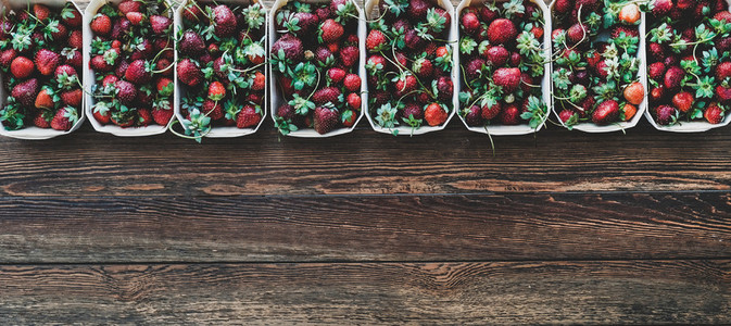 Fresh strawberries in plastic free containers over wooden background  wide composition