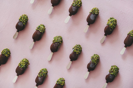 Chocolate glazed popsicle ice cream with pistachio icing over pink background