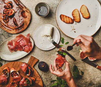 Crostini with prosciutto  grilled figs  cheese and hands with canape