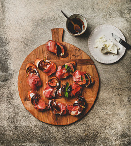 Crostini with prosciutto  cheese  figs over concrete table  top view