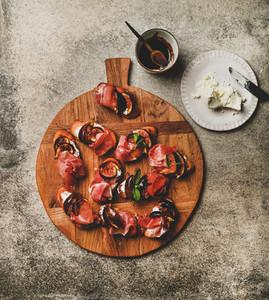 Crostini with prosciutto cheese figs over concrete table top view