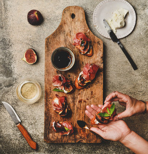 Crostini with prosciutto cheese and figs and female hands